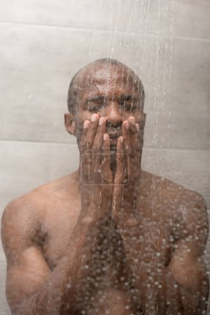 handsome african american man washing body in shower