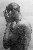 side view of young african american man washing body in shower, black and white photo