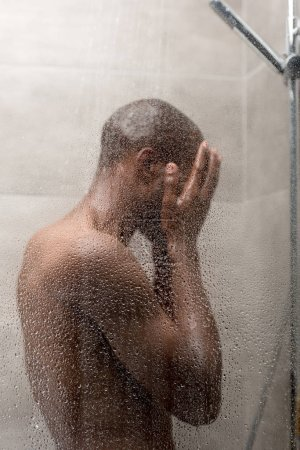 side view of young african american man washing body in shower