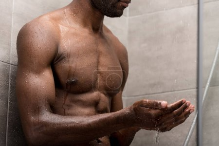cropped shot of young african american washing body and taking shower