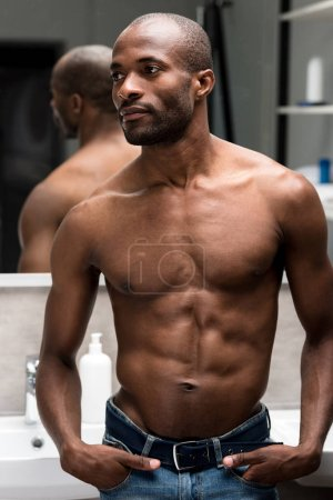 handsome shirtless african american man standing with hands in pockets and looking away in bathroom