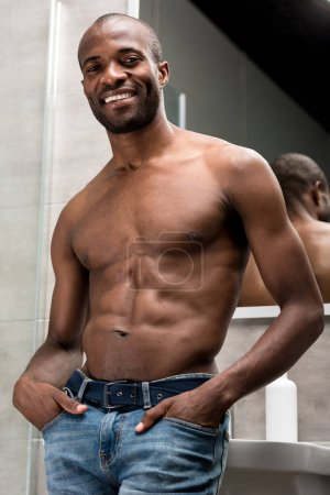 low angle view of handsome shirtless african american man standing with hands in pockets and smiling at camera in bathroom