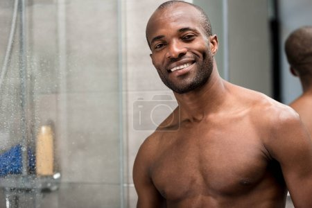 handsome bare-chested african american man standing in bathroom and smiling at camera