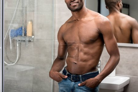 cropped shot of smiling standing african american man standing with hands in pockets in bathroom