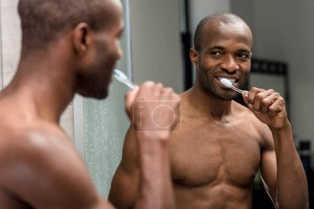 selective focus of smiling shirtless african american man brushing teeth and looking at mirror