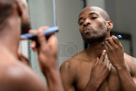 cropped shot of young african american man shaving with electric trimmer and looking at mirror
