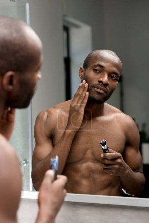 cropped shot of handsome african american man holding trimmer and looking at mirror in bathroom