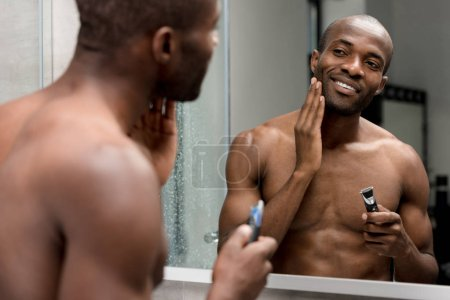 smiling african american man shaving with electric trimmer in bathroom