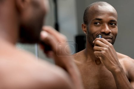 selective focus of african american man shaving with electric trimmer in bathroom