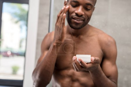 smiling shirtless young african american man applying facial cream in bathroom