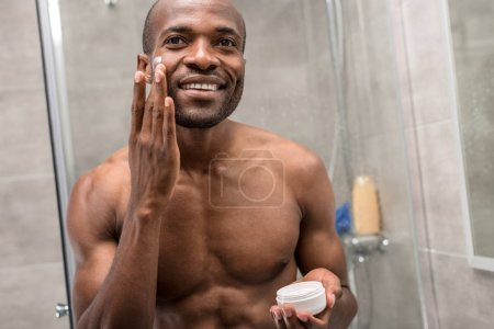 handsome smiling young african american man applying facial cream in bathroom