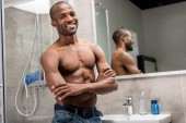 young bare-chested african american man standing with crossed arms and smiling at camera in bathroom