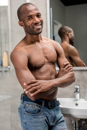 handsome shirtless african american man standing with crossed arms and smiling at camera in bathroom