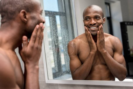 smiling shirtless african american man applying shaving lotion and looking at mirror