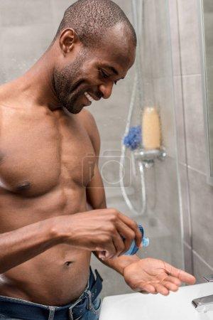 smiling shirtless african american man applying lotion in bathroom