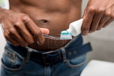close-up partial view of young african american man holding toothbrush and toothpaste