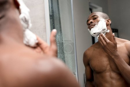 cropped shot of handsome african american man shaving and looking at mirror