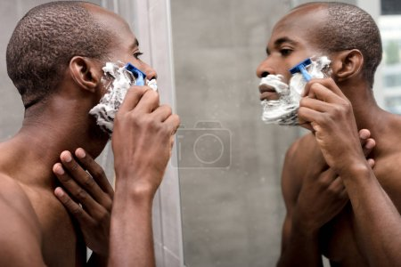 handsome african american man shaving and looking at mirror