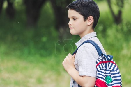 Photo for Thoughtful schoolboy with backpack looking away at park - Royalty Free Image