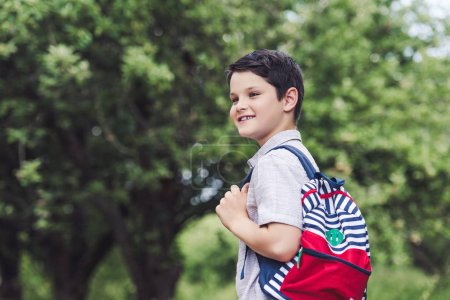happy schoolboy with backpack looking away in park