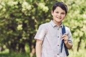 smiling schoolboy with backpack looking at camera outdoors