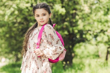 beautiful schoolgirl in dress with backpack looking at camera in park