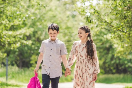 adorable kids holding hands and walking by park