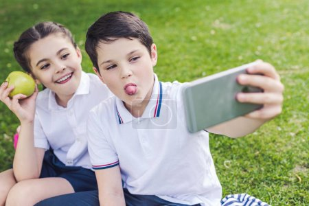 schoolchildren grimacing and taking selfie while sitting on grass in park