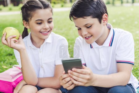 smiling schoolchildren using smartphone together while sitting on grass