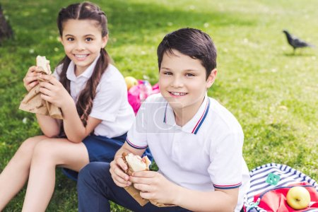 smiling schoolchildren sitting on grass and eating sandwiches