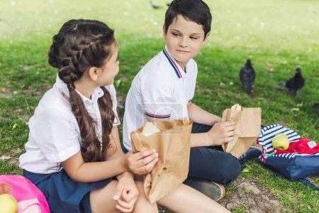 happy schoolchildren sitting on green grass and taking lunch
