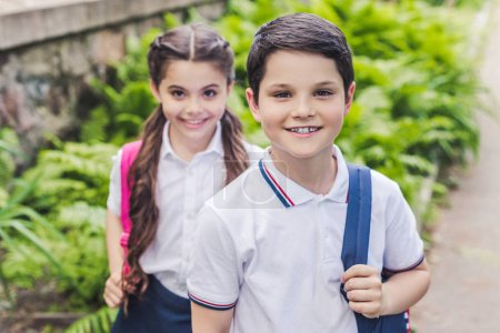 adorable schoolchildren with backpacks looking at camera in park