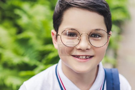 close-up portrait of happy kid in round eyeglasses looking at camera