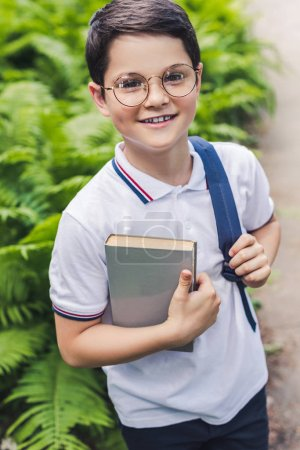happy schoolboy with backpack and book looking at camera in garden