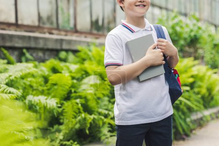 Photo for Cropped shot of schoolboy with backpack and book in garden - Royalty Free Image