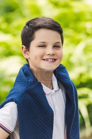 smiling kid with jumper over shoulders looking at camera