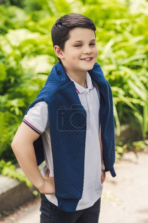 happy kid with jumper over shoulders looking at camera