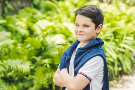 stylish kid with jumper over shoulders looking at camera with crossed arms
