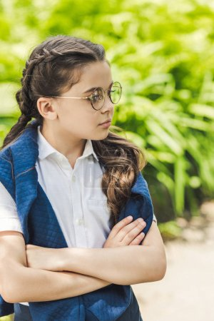 serious schoolgirl with crossed arms in white shirt and jumper over shoulders looking away