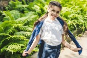 happy schoolgirl in white shirt and jumper over shoulders