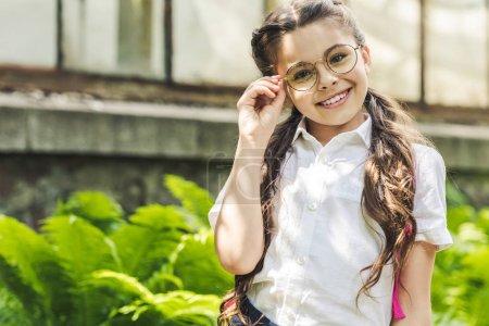 beautiful schoolgirl in uniform and eyeglasses looking at camera in park