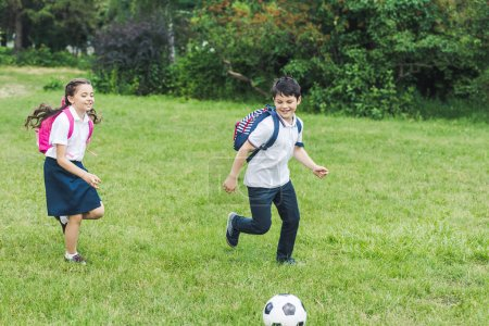 schoolchildren with backpacks playing soccer together on meadow in park
