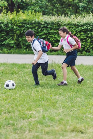 active schoolchildren playing soccer together on meadow in park