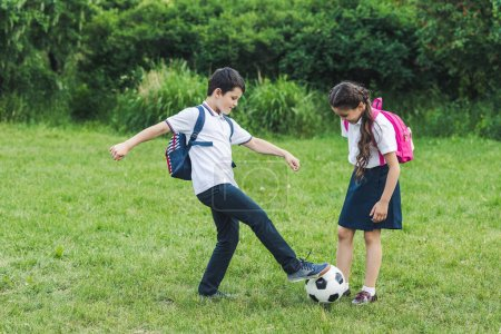 happy schoolchildren playing soccer together on meadow in park