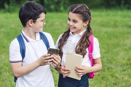 smiling schoolchildren using smartphone outdoors together