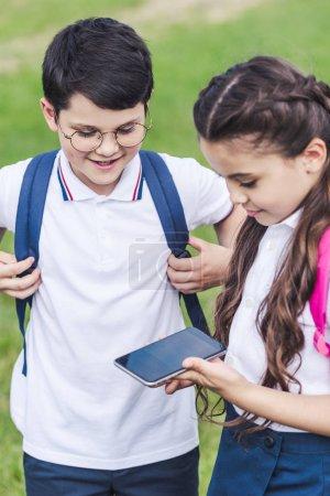 happy schoolchildren using smartphone outdoors together