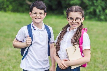 happy schoolchildren in eyeglasses looking at camera on meadow in park
