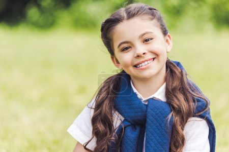 close-up portrait of beautiful schoolgirl in stylish clothes in park