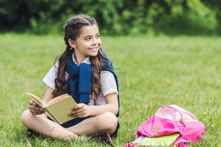 smiling schoolgirl with book sitting on grass in park and looking away
