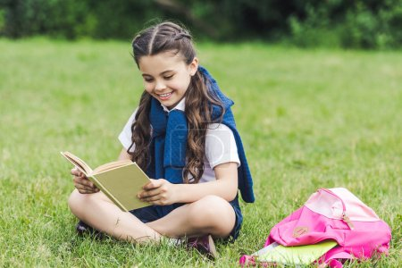 happy schoolgirl reading book while sitting on grass in park